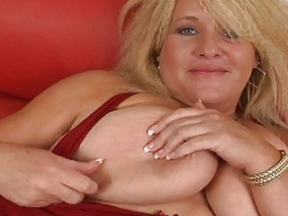 giant blond momma with huge bosom plays on sofa