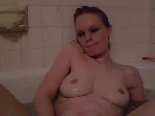 busty single woman pleasing into the bathtub